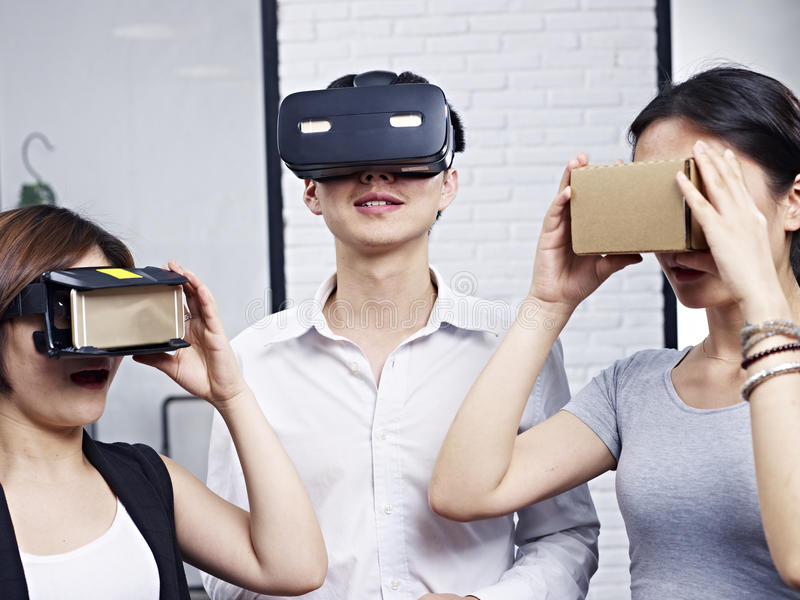 Young asian people trying virtual reality goggles stock images