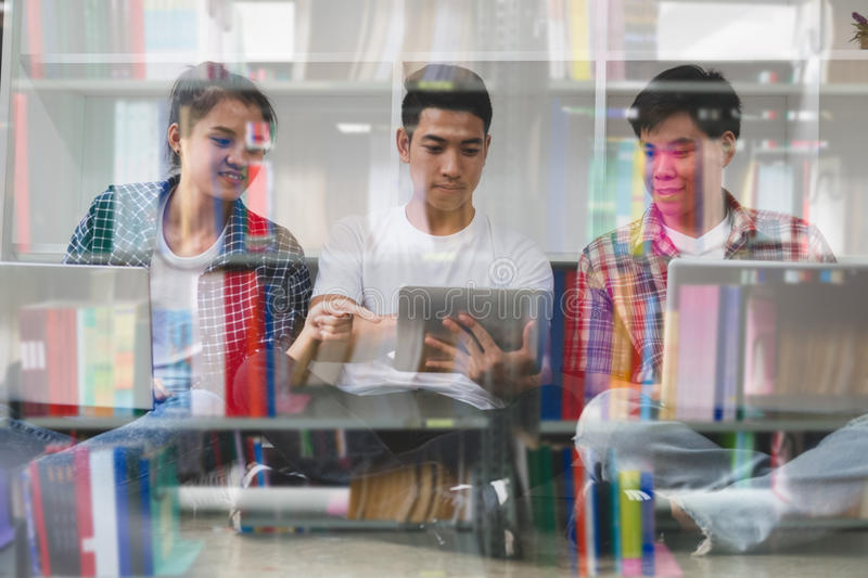 young asian people are using different gadgets and smiling, sitting near white wall. Male and female students studying using stock images