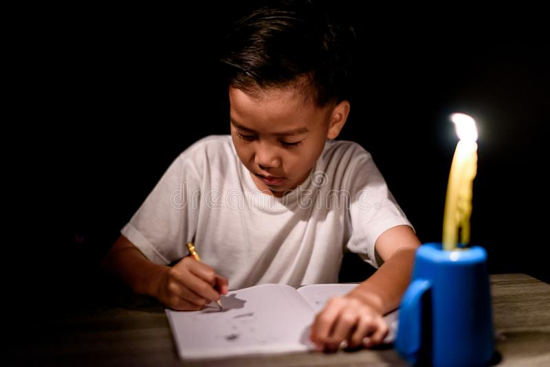 Young boy do home work under candle light royalty free stock images