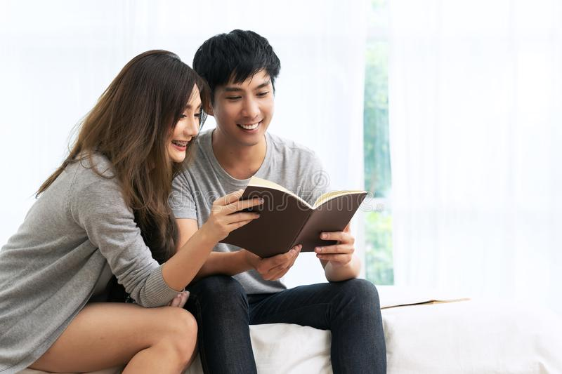 Young asian romantic couple reading book having great time together feeling satisfaction and positive in white bedroom. Close up royalty free stock photo
