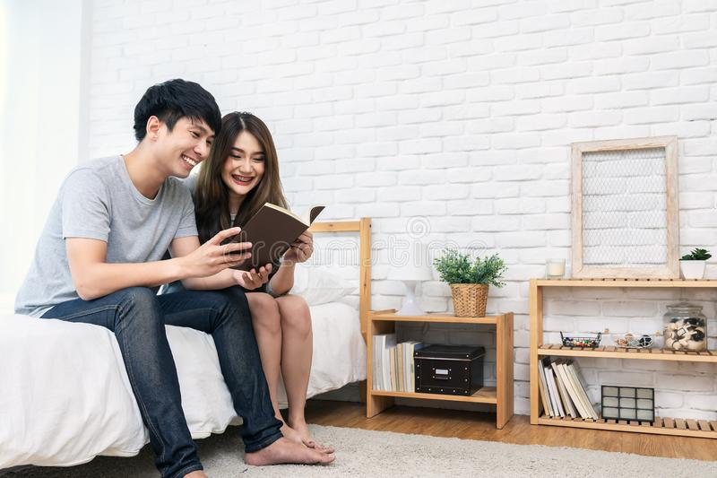 Young asian romantic couple reading book having great time together feeling satisfaction and positive in white bedroom stock photo