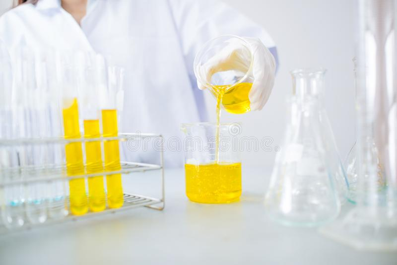 Young Asian scientist with test tube making research in clinical laboratory.Science, chemistry, technology, biology and people con. Oil pouring, Formulating the stock photos