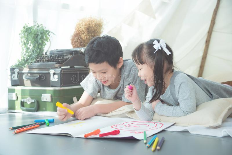 Siblings lying on the floor and drawing picture by crayon stock photo