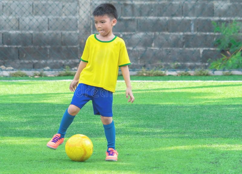 Young soccer player with yellow ball on training field stock photography