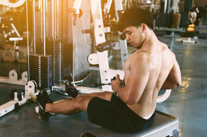 Young asian sportsman pull still weight for building muscle at i stock photo