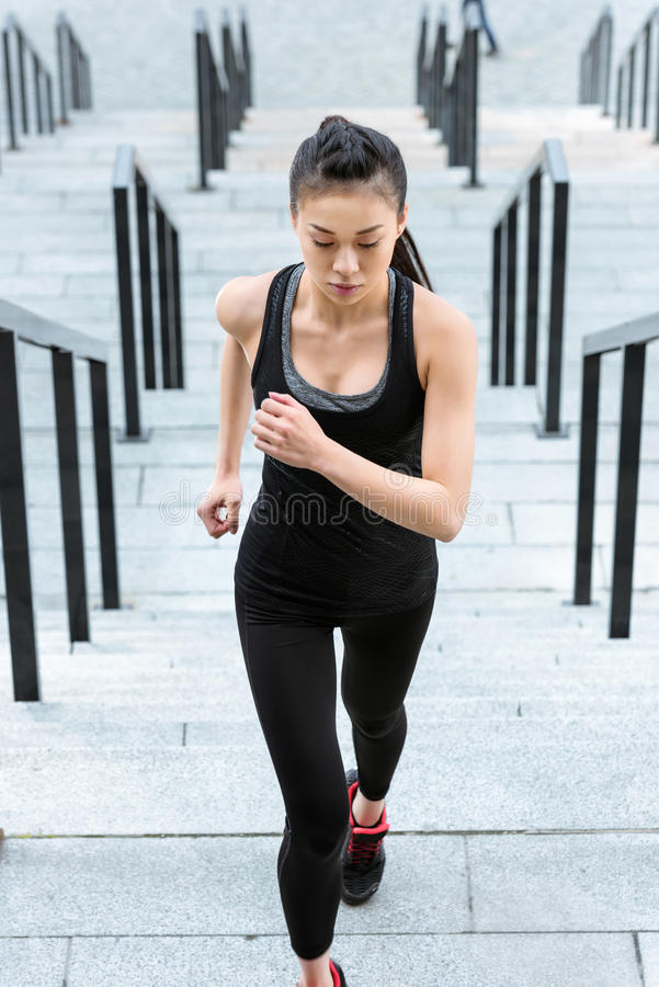 Young asian sportswoman running up on stadium stairs royalty free stock photography
