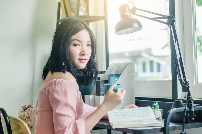 Young asian student with cup of coffee opening and reading a book on wooden table at home stock photo