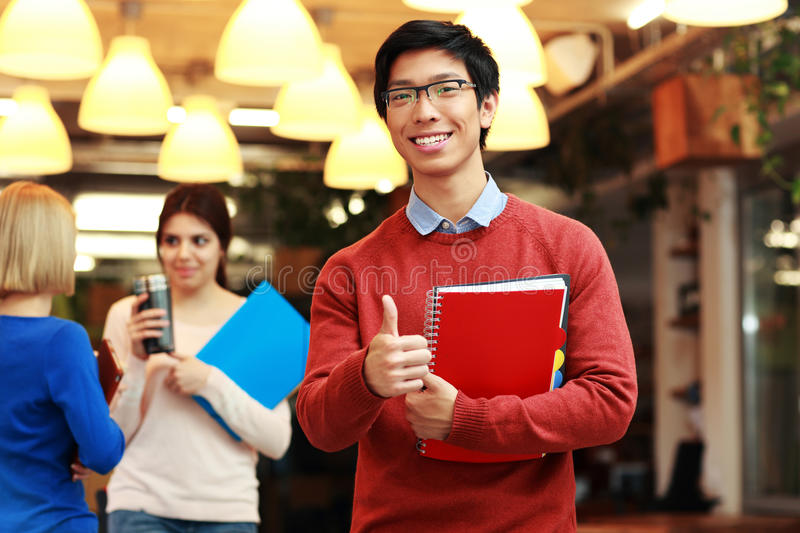 Young asian student doing thumbs up. Handsome young asian student doing thumbs up in front of a group of students royalty free stock image
