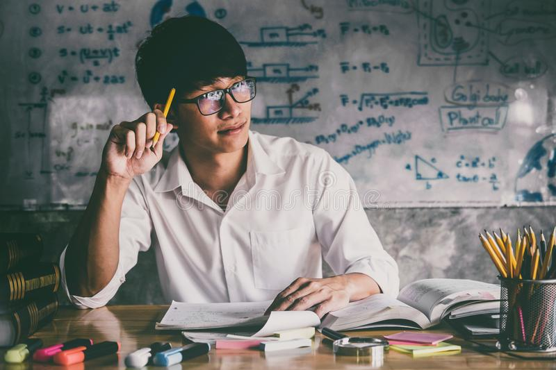 Young Asian student man sitting at desk in home studying and reading, doing homework and lesson practice preparing exam to. Entrance, education concept royalty free stock image