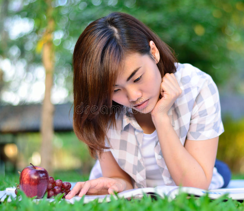 Young asian student is reading. Beautiful young asian student is reading and eating stock photography
