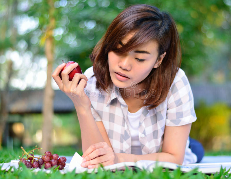 Young asian student is reading. Beautiful young asian student is reading and eating royalty free stock image