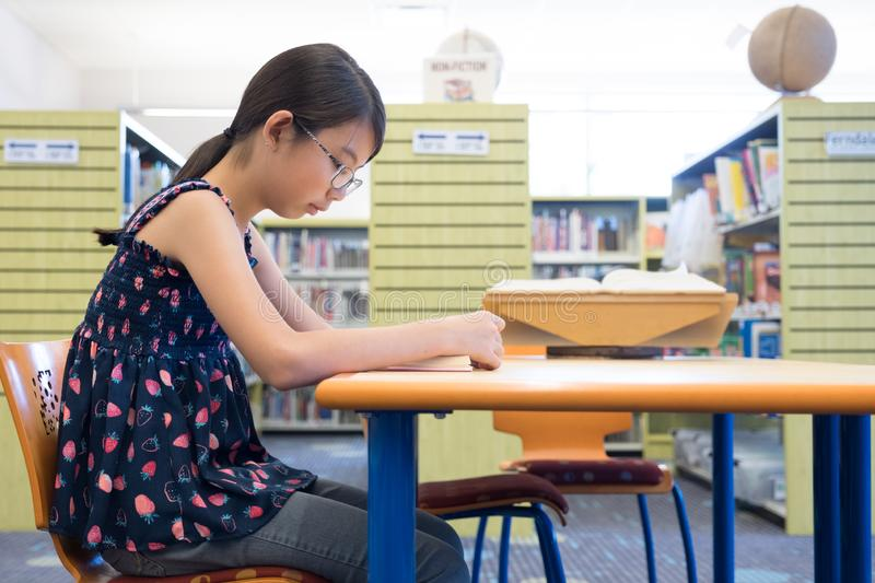 Young Asian student reading a book in library royalty free stock photos