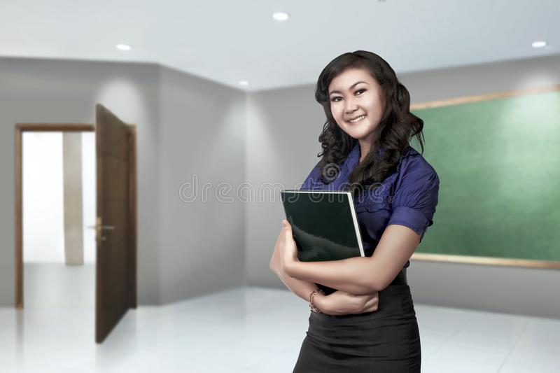 Young asian teacher woman with book in her hand stock image