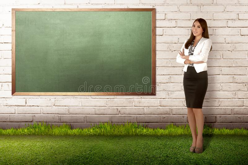 Young asian teacher woman standing with empty chalkboard royalty free stock photo