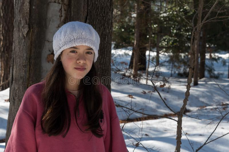 Young Asian teen in white knit cap. In winter snow stock image