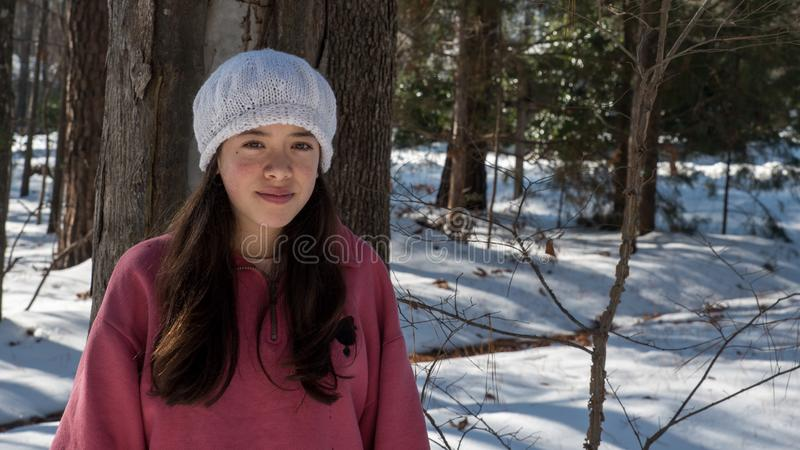 Young Asian teen in white knit cap. In winter snow stock photo