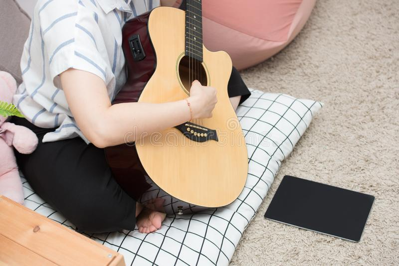 Young asian teenager brunette girl with long hair sitting on the floor and playing an black acoustic guitar on gray wall stock photos