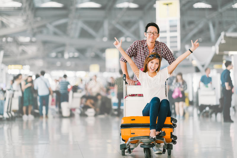 Asian tourist couple happy and excited together for the trip, girlfriend sitting and cheering on baggage trolley or luggage cart stock photography
