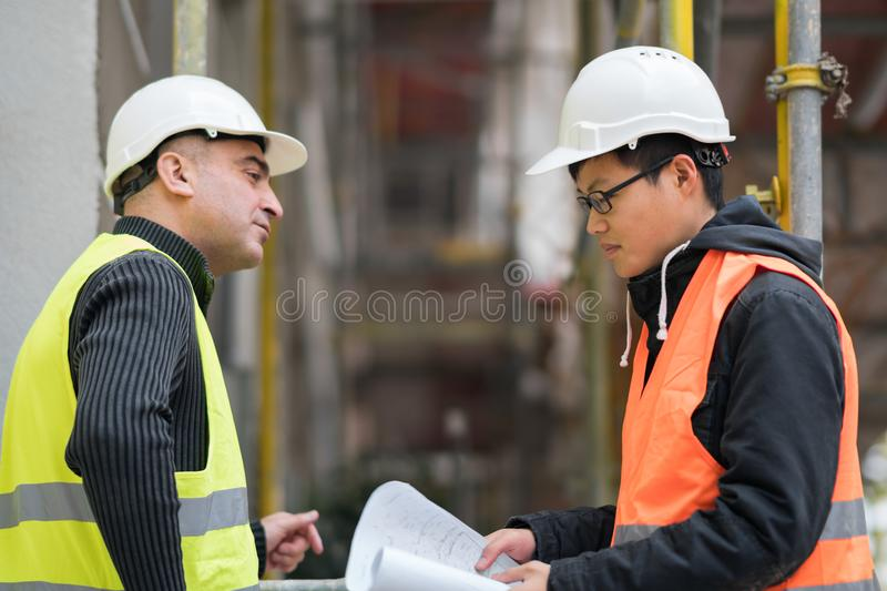 Asian apprentice engineer at work on construction site with the senior manager. Young Asian trainee engineer at work on construction site with the senior manager stock photos