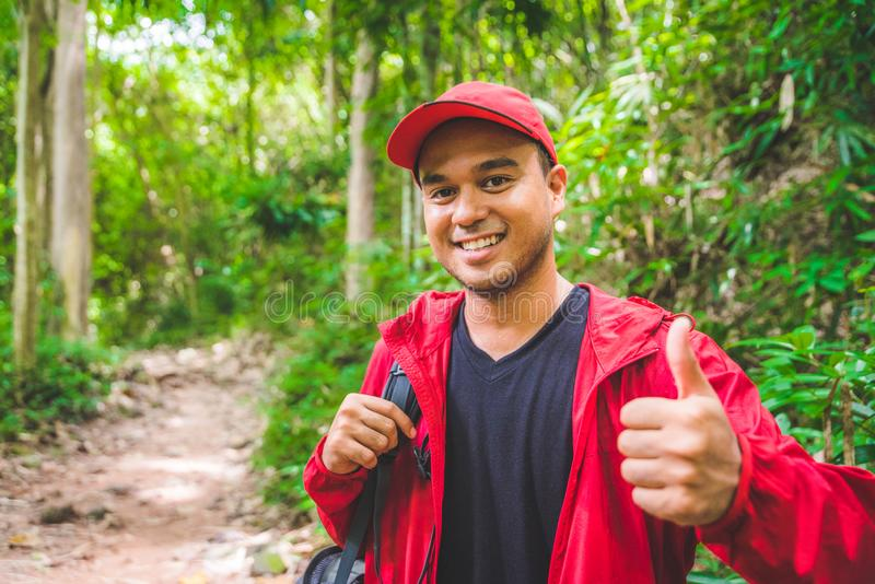 Young asian travel handsome man hiking in forest and mountain enjoy walking in nature outdoors. Image of lifestyle camping,travel, royalty free stock photo