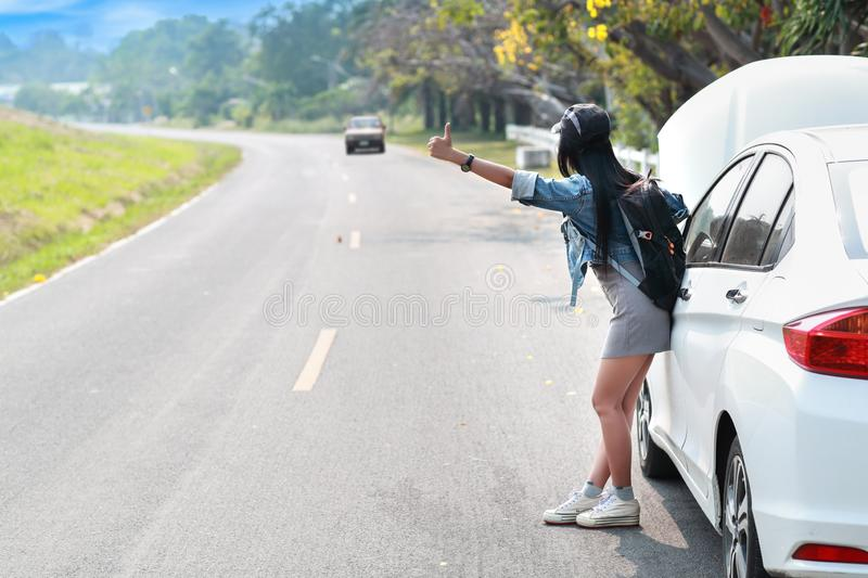 Young asian traveler with backpack and map hitchhiking on the road while traveling during holiday vacation stock photo
