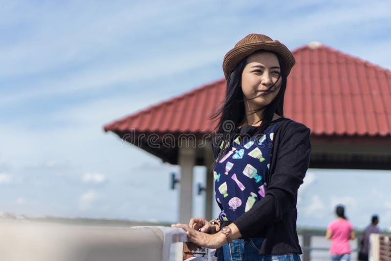 Young Asian traveler girl chilling in the sun beside river and Waterfront pavilion and red roof. Outdoors portrait of young asia girl at natural background stock photos