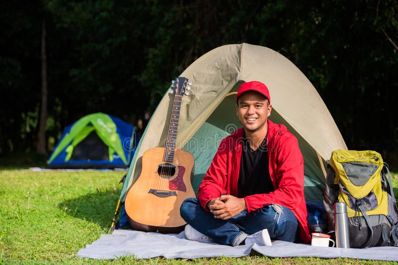 Young asian traveler man camping with tent in nature. Backpacker, Relaxing, Holiday, Activities, Hiking concept with copy space. stock images
