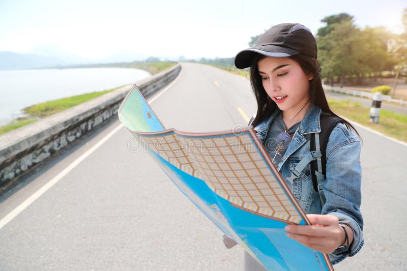 Young asian traveler searching direction on location map while traveling during holiday vacation stock images