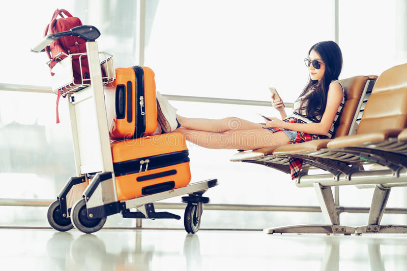 Young Asian traveler woman, university student sit using smartphone at airport, luggage and bag on trolley cart. Young Asian traveler woman, university student royalty free stock photo