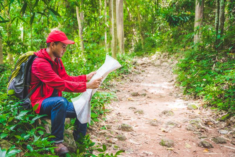 Young asian traveller man searching right direction on map in the forest. Image of lifestyle camping,travel,hiking or recreation c royalty free stock photography
