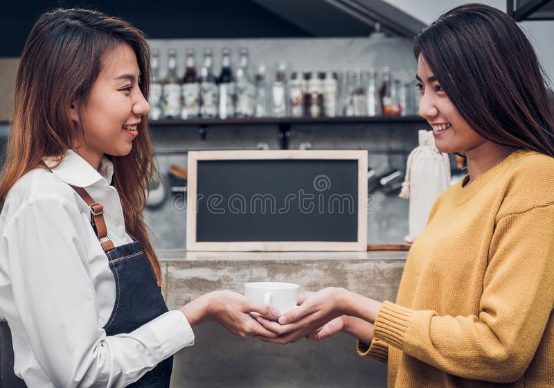 Young asian woman barista hold coffee cup serving a client at the coffee shop,start up small business owner food and drink concept royalty free stock photography