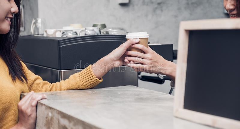 Young asian woman barista wear jean apron served to go coffee cup to customer at bar counter with smile emotion,Cafe restaurant royalty free stock photos