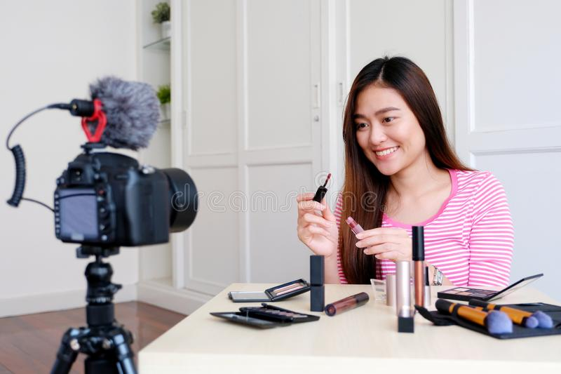 Young asian woman beauty blogger showing cosmetic while recording how to make up video tutorial by camera, vlog concept, beauty stock photo