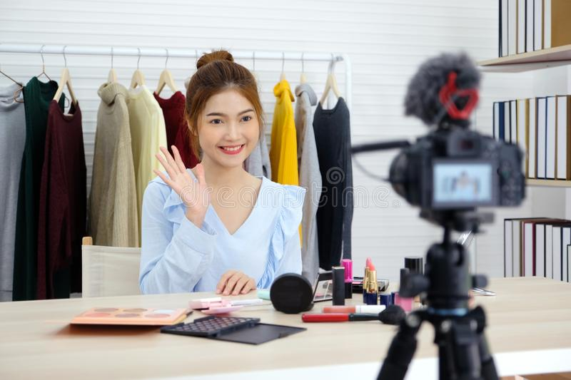 Young asian woman beauty blogger showing how to make up video tutorial recording by camera, vlog concept, fashion people and stock images