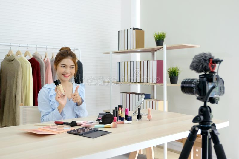 Young asian woman beauty video blogger thumb up and showing cosmetic for make up, beauty fashion vlog concept, people and royalty free stock photography