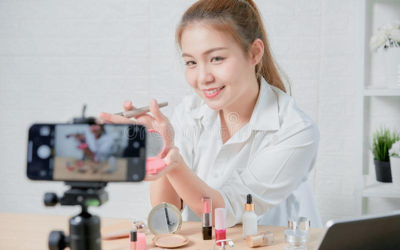 Young Asian woman beauty vlogger video online is showing make up on cosmetics products and live video on digital smartphone. stock photos