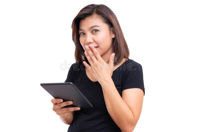 Young asian woman black hair holding tablet computer. Woman saying hush be quiet with finger on lips gesture isolated royalty free stock photography