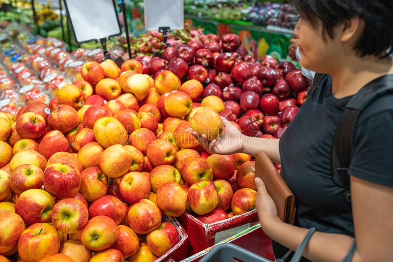 Young Asian woman buying apple at fruit stand in supermarket stock photography