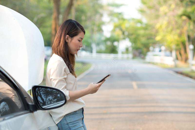 Young Asian woman calling assistance for her broken down car stock photography