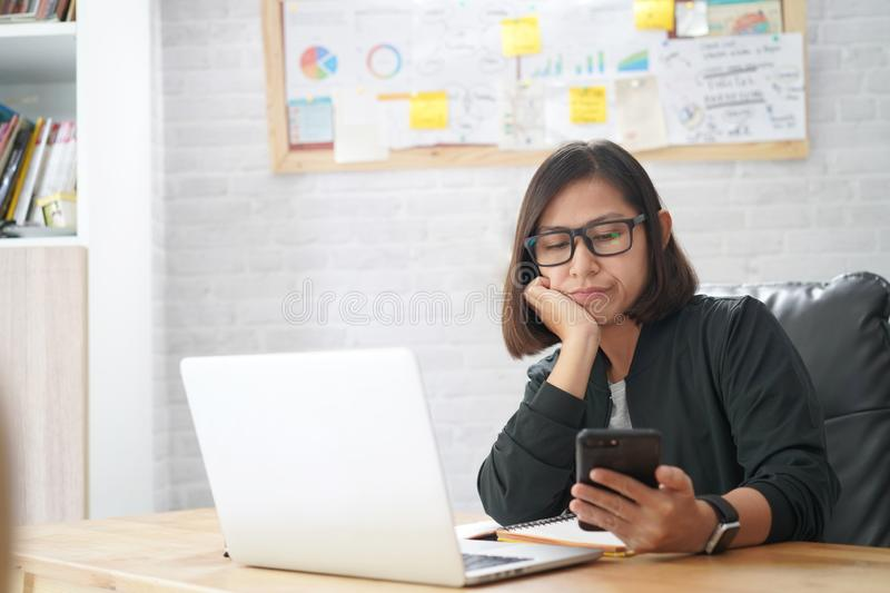 Young asian woman checking reading smart phone repetitious bored news royalty free stock photography