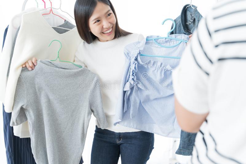 Young Asian woman choosing clothes on a rack . shopping buying fashion concept. royalty free stock photos