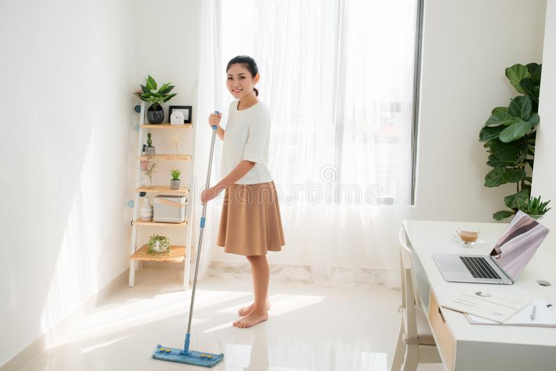 Young Asian woman cleaning floor at home doing chores with attractive smile on face stock images