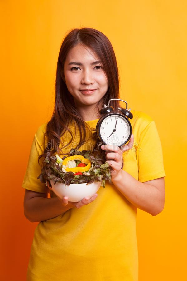 Young Asian woman with clock and salad in yellow dress royalty free stock image