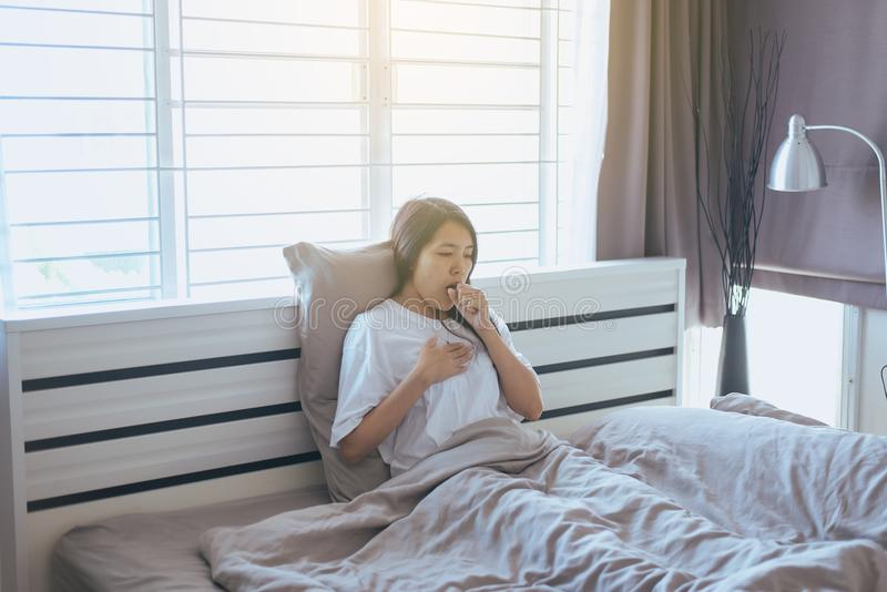 Young asian woman coughing and sitting on her bed stock images