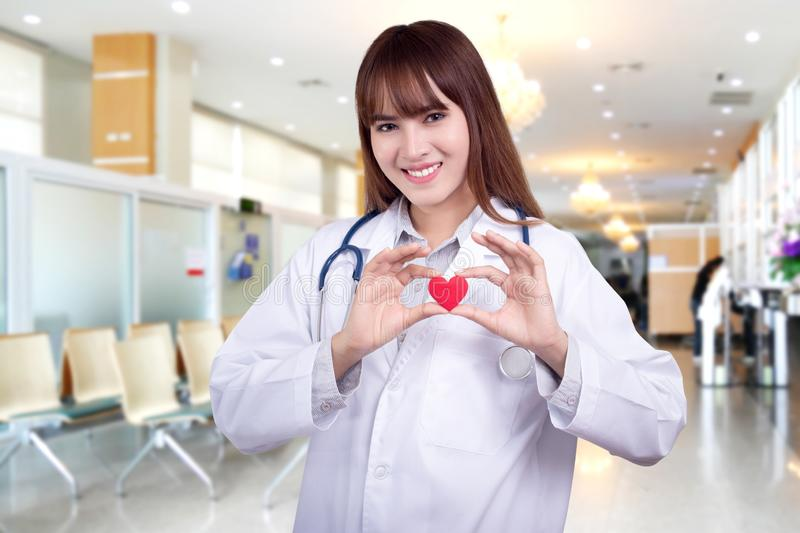 Young Asian woman doctor holding a red heart, standing on hospital background. healthy care concept royalty free stock images