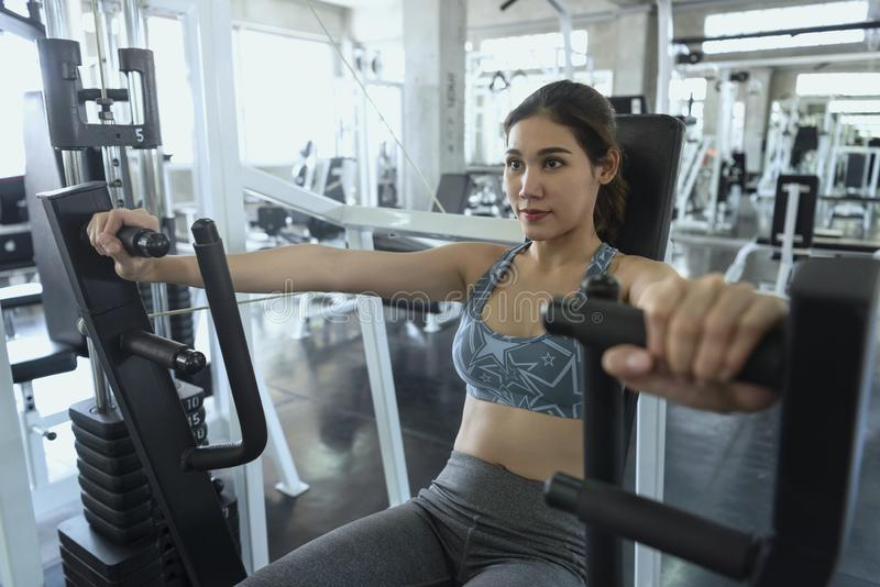 Young asian woman doing exercises for chest in gym. healthy lifestyle and workout motivation concept. ใ stock photography
