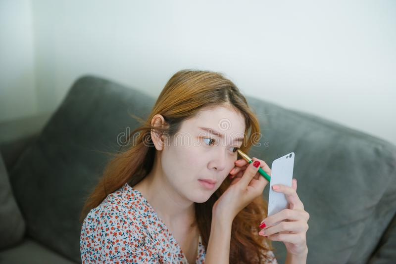 Young asian woman doing makeup with cosmetic pencil at home. royalty free stock images