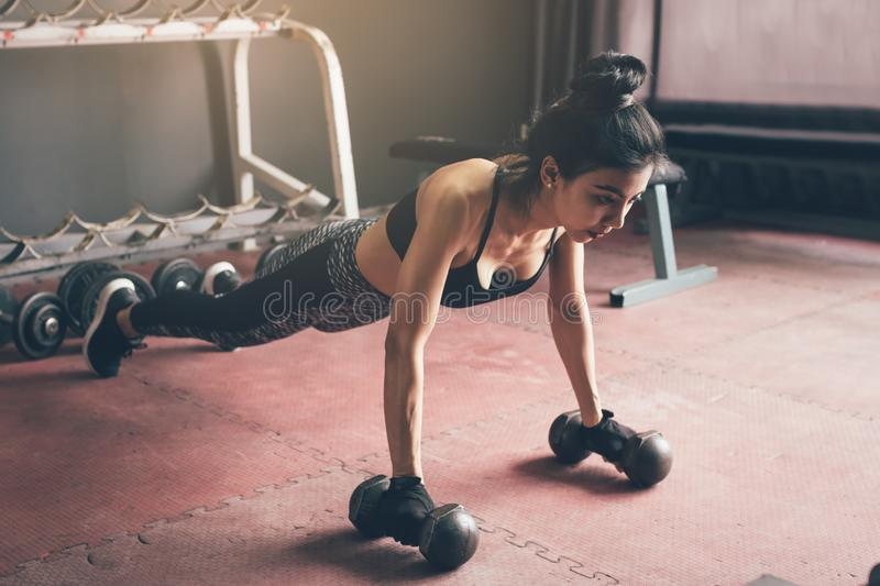 Young asian woman doing push-ups on dumbbell in a gym. royalty free stock photography