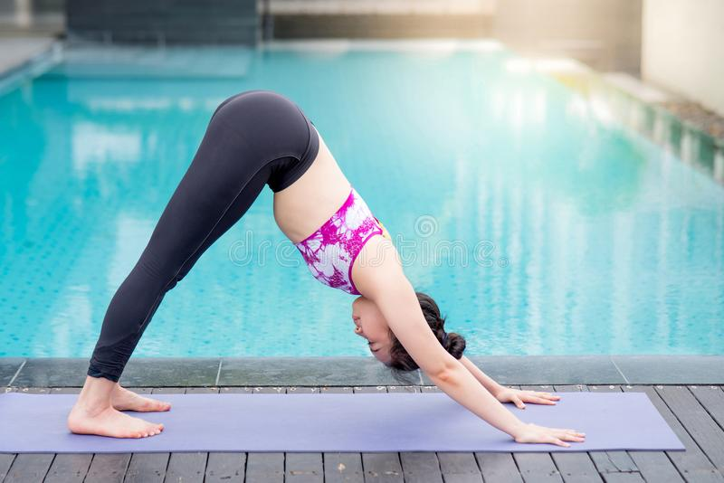 Young Asian woman doing yoga exercise with downward facing dog p stock photography