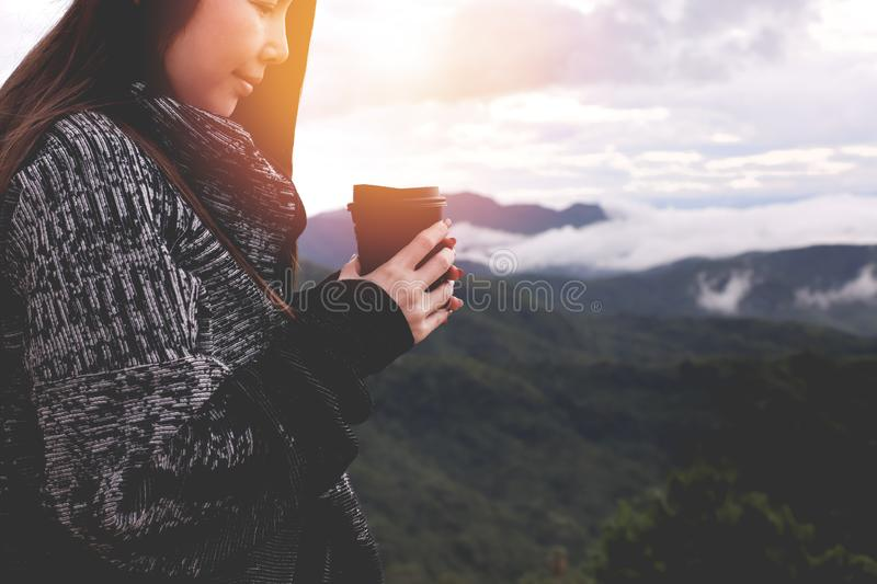 Young asian woman drinking hot coffee on scenery view in winter morning. Young asian woman drinking hot coffee on scenery view in morning stock photography
